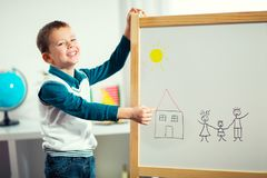 Cute little boy drawing on white board with felt pen and smiling Royalty Free Stock Images