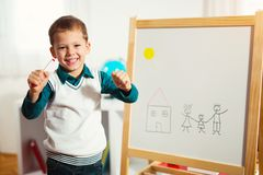 Cute little boy drawing on white board with felt pen and smiling. Early education concept stock photo