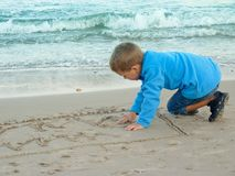 Little boy draws on sand stock photos