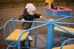 Cute little boy dressed in a warm hat and jacket riding on the c royalty free stock image