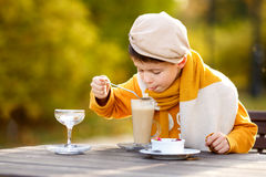 Cute little boy drinking hot chocolate in outdoor cafe royalty free stock photos