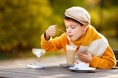 Cute little boy drinking hot chocolate in outdoor cafe Royalty Free Stock Image