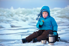 Cute little boy drinking hot tea in winter royalty free stock images