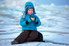 Cute little boy drinking hot tea in winter beach Stock Images