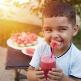 Cute little boy drinking juice in the garden royalty free stock photography