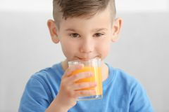 Cute little boy drinking juice at home Stock Photography