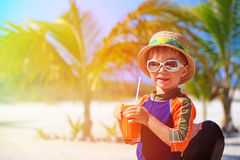 Cute little boy drinking juice on tropical beach Royalty Free Stock Image
