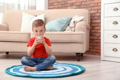Cute little boy drinking milk on floor. At home royalty free stock photography