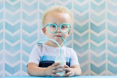 Cute little boy drinking milk with funny glasses straw. royalty free stock photo