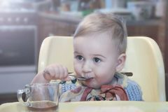 Cute little boy drinking tea from a mug with a spoon while sitting in a chair Stock Photo