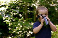 Boy drinking water. Cute little boy drinking water from a bottle in the forest stock photos