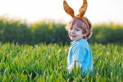 Cute little boy with Easter bunny ears  in green grass Royalty Free Stock Photo