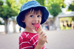Cute little boy, eating big ice cream in the park, smiling at ca Royalty Free Stock Photo