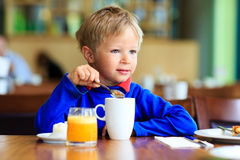 Cute little boy eating breakfast in cafe Royalty Free Stock Photo