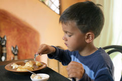 Cute little boy eating breakfast. Little five year old boy eating cottage cheese cheesecakes for Breakfast Stock Photos