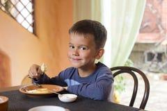 Cute little boy eating breakfast Stock Photos