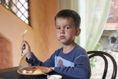 Cute little boy eating breakfast Royalty Free Stock Image
