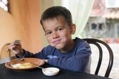 Cute little boy eating breakfast Stock Photo