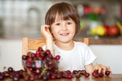 Cute little boy, eating cherries at home in the kitchen, making Royalty Free Stock Photography