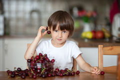 Cute little boy, eating cherries at home in the kitchen, making Stock Image