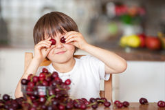 Cute little boy, eating cherries at home in the kitchen, making. Funny faces and playing with the cherries, having fun Stock Photography