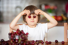 Cute little boy, eating cherries at home in the kitchen, making Stock Photos