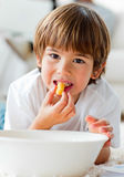 Cute little boy eating chips lying on the floor Royalty Free Stock Images