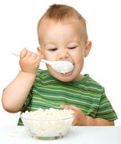 Cute little boy is eating cottage cheese Stock Photography