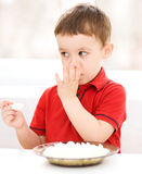 Cute little boy is eating cottage cheese Royalty Free Stock Photography