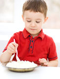 Cute little boy is eating cottage cheese Royalty Free Stock Photos