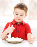 Cute little boy is eating cottage cheese Stock Image