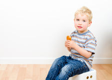 Cute little boy eating delicious cookie at home Stock Photo