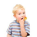 Cute little boy eating delicious cookie isolated Stock Image