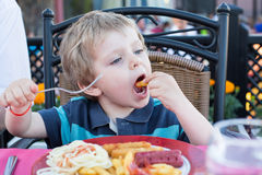 Cute little boy eating french fries in summer Stock Photo