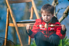 Cute little boy eating grilled vegetables Royalty Free Stock Photos