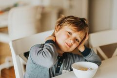 Cute little boy eating his cereals with milk stock images