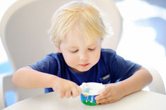 Cute little boy eating Ice-Cream gelato in Italian indoors cafe Royalty Free Stock Images