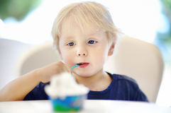 Cute little boy eating Ice-Cream gelato in Italian indoors cafe Royalty Free Stock Photos