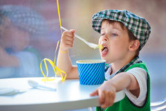 Cute little boy eating ice cream at indoor cafe Stock Photo