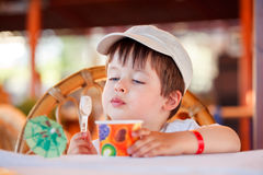 Cute little boy eating ice cream at indoor cafe Stock Photography