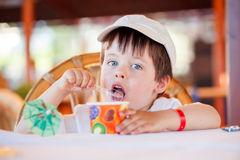 Cute little boy eating ice cream at indoor cafe Royalty Free Stock Photos