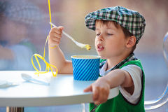 Cute little boy eating ice cream at indoor cafe Royalty Free Stock Image