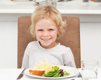 Cute little boy eating pasta and salad Stock Images