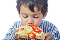 Cute little boy eating pizza Stock Photos