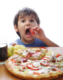 Cute little boy eating pizza Stock Images