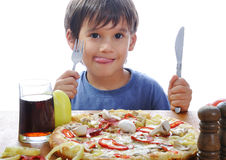 Cute little boy eating pizza on table Royalty Free Stock Image