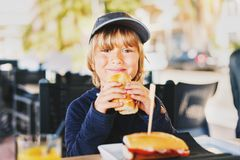 Cute little boy eating sandwich for breakfast Royalty Free Stock Photos
