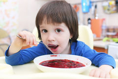 Cute little boy eating soup Stock Photo