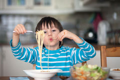 Cute little boy, eating spaghetti at home for lunchtime Royalty Free Stock Photos