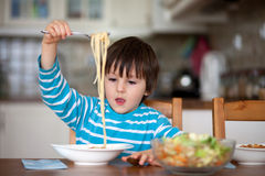 Cute little boy, eating spaghetti at home for lunchtime Royalty Free Stock Image